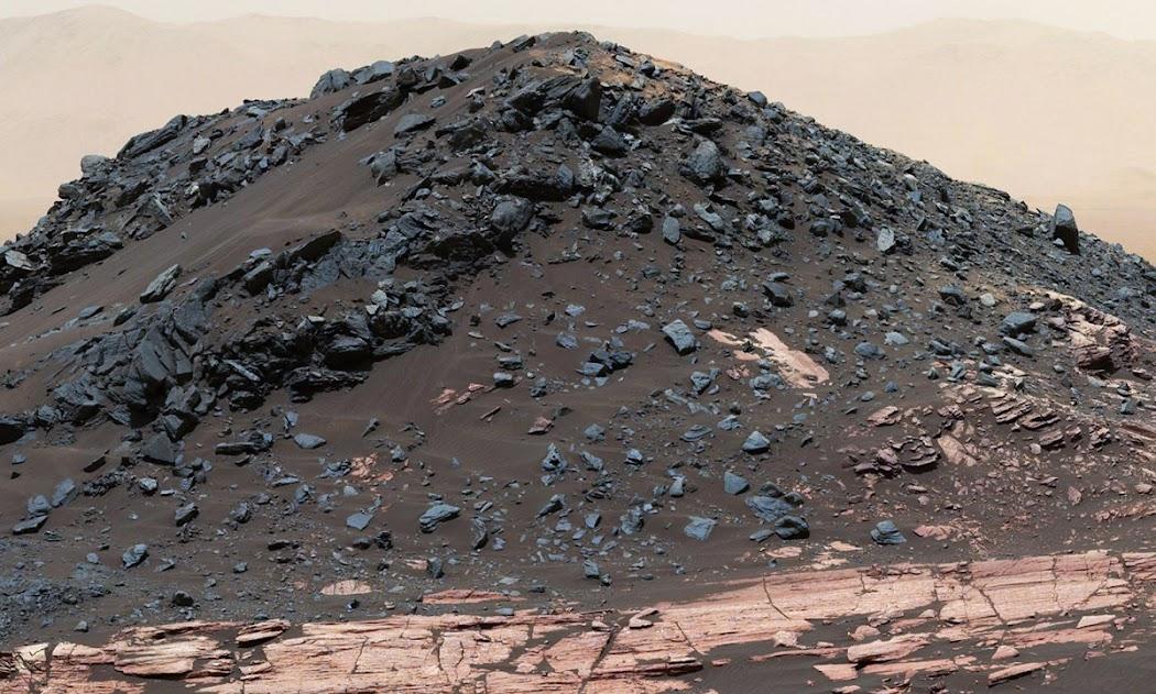 Vùng đồi tối màu này được gọi là Đồi Ireson, cao khoảng 5 mét so với lớp đá đỏ bề mặt bên dưới thuộc hệ thống Đồi Murray ở vùng chân của Núi Sharp. Nơi này gần với địa điểm mà tàu Curiosity của NASA gần đây đã ghé lại để nghiên cứu một cồn cát nhỏ vào ngày 2 tháng 2 năm 2017, tức là sol 1598. Ở xa xa, bạn có thể thấy được một phần của rặng núi bao xung quanh Hố va chạm Gale. Hình ảnh: JPL-Caltech/MSSS/NASA.