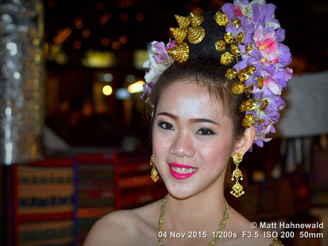 Matt Hahnewald; Facing the World; people; photo; colour; night; street portrait; Asia; Northern Thailand; Chiang Rai; dancer; beautiful; eye contact; posing; travel; Thai beauty; close up; floral hair wreath; tourism; smiling; blue; red lips; make-up; drop earrings; gold