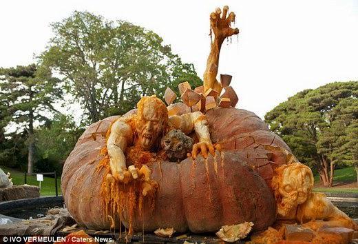 تمثال تم نحته لعيد الهاليون يضم يقطينة ضخمة ورجال يخرجون منها على شكل زومبي وهياكل عظمية