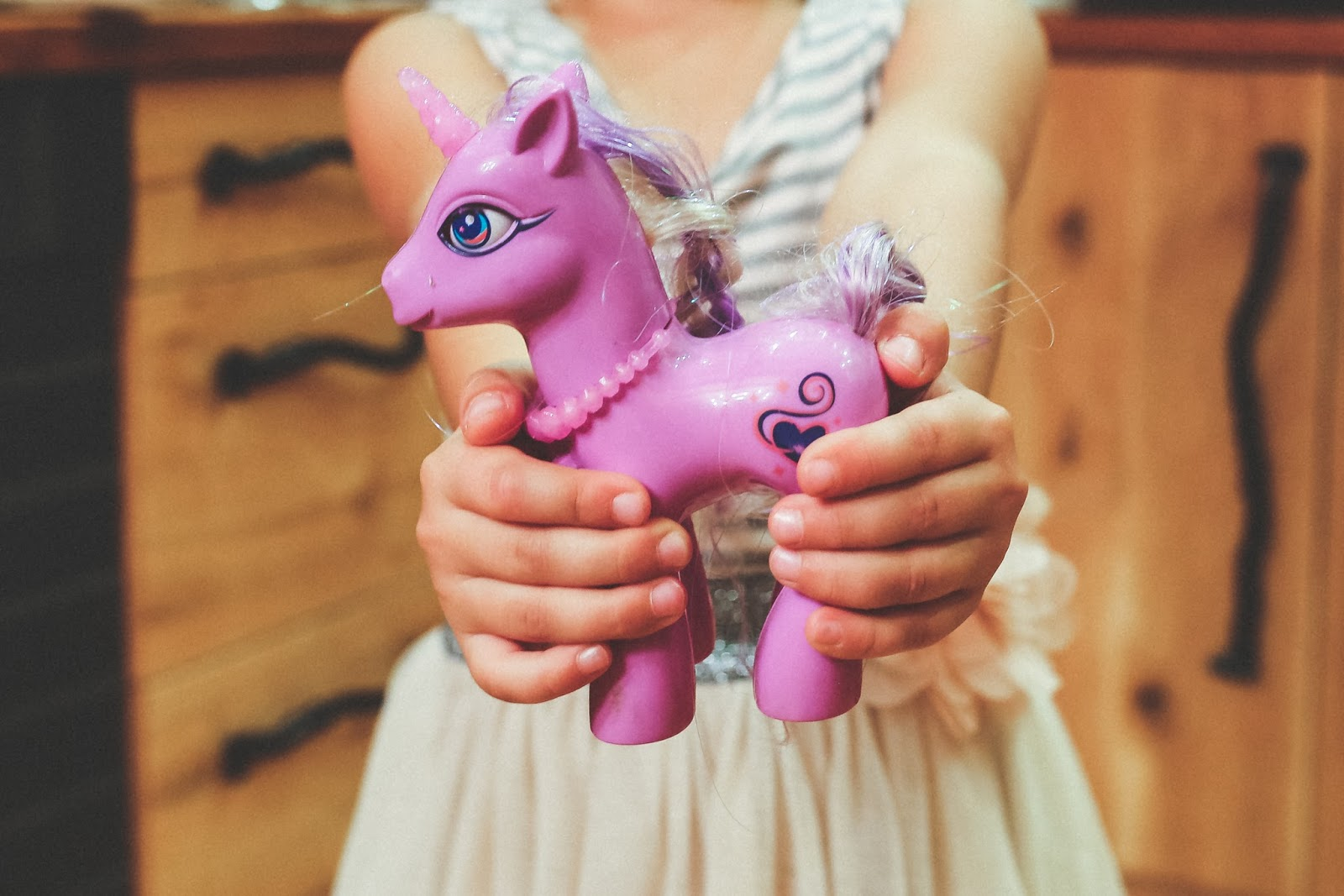 Little girl's hands holding a pink My Little Pony