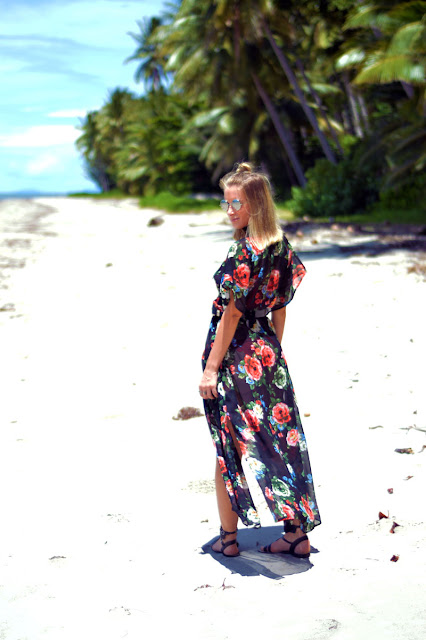 blonde fashion blogger on white sand beach wearing black floral kimono dress