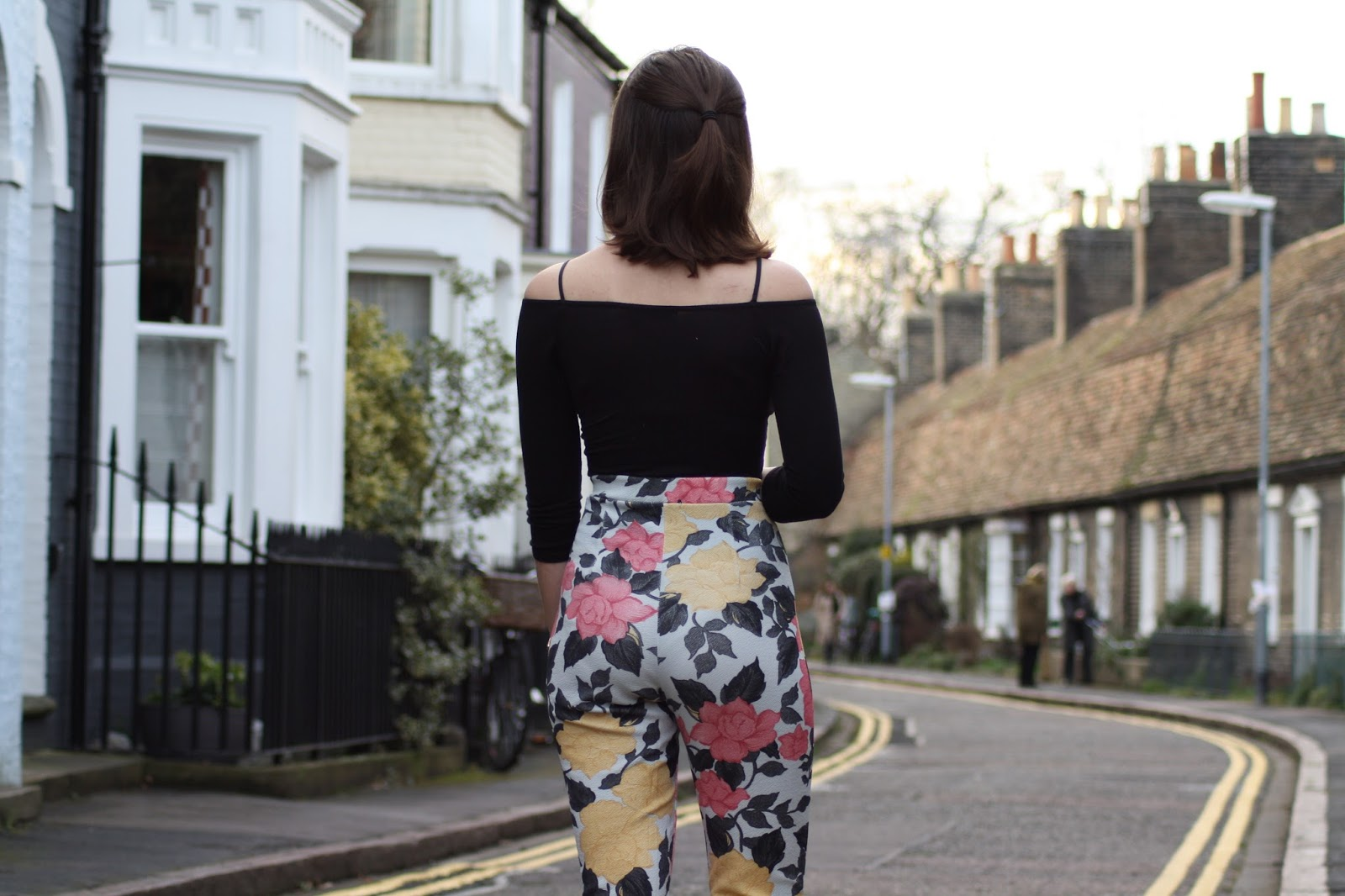 Abbey, a bloggerer, stands facing away from the camera, wearing floral trousers and a black off-shoulder top