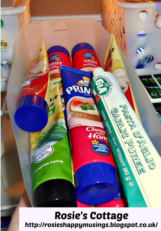 Refrigerator organization using bins - tubes of cheeses & garlic and tomato purees.