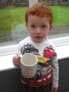 Little boy holding up the decorated mug