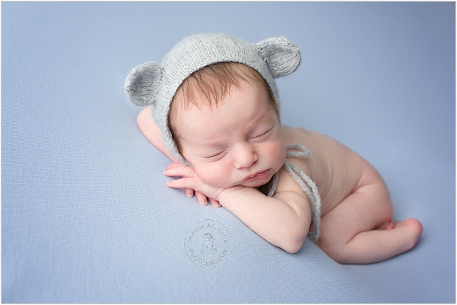 Newborn baby boy is posed on a blue blanket with his head on his hands.