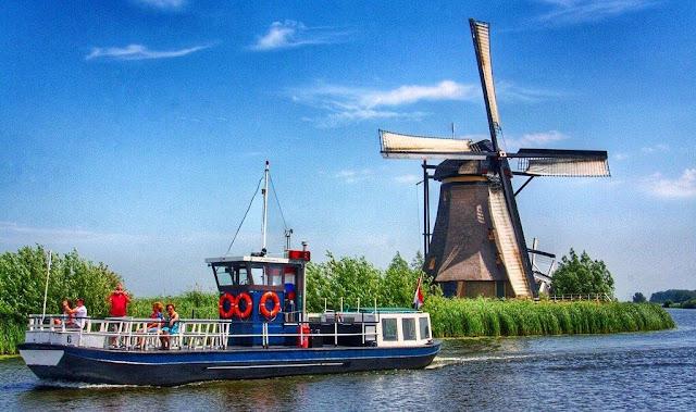 Molino holandes y barco en canal de Kinderdijk en los Paises Bajos