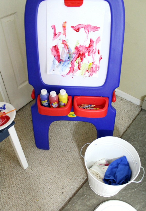 Organized art station for kid's art and craft supplies: Use a small Ikea trash can to store a sheet and smock for easy painting setup and cleanup