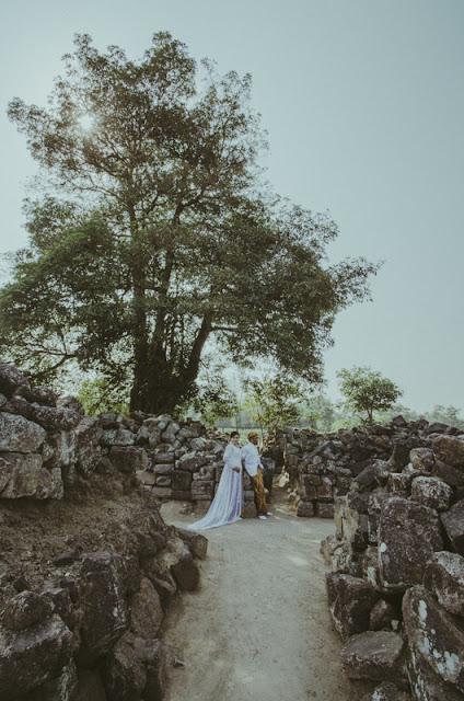 Prewedding Desi dan Rudi di Candi Plaosan Yogyakarta, menggunakan pakaian tradisional Jawa (kebaya) berwarna putih, dan jarik untuk Rudi berwarna kuning keemasan. Lokasi berada di bawah pohon besar di bagian pinggir kawasan candi.