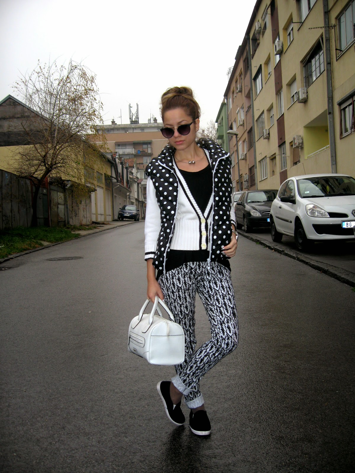 outfit, black and white, black and white pants, feather print pants, polka dots puffer vest, black and white sweater, black slip ons, messy bun