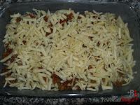 Añadiendo la mitad del queso rallado