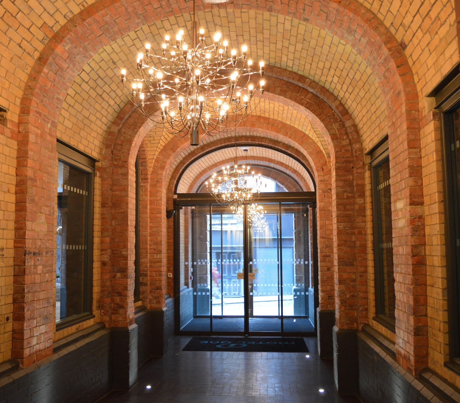 Motel One Lobby Newcastle - exposed brickwork and chandelier
