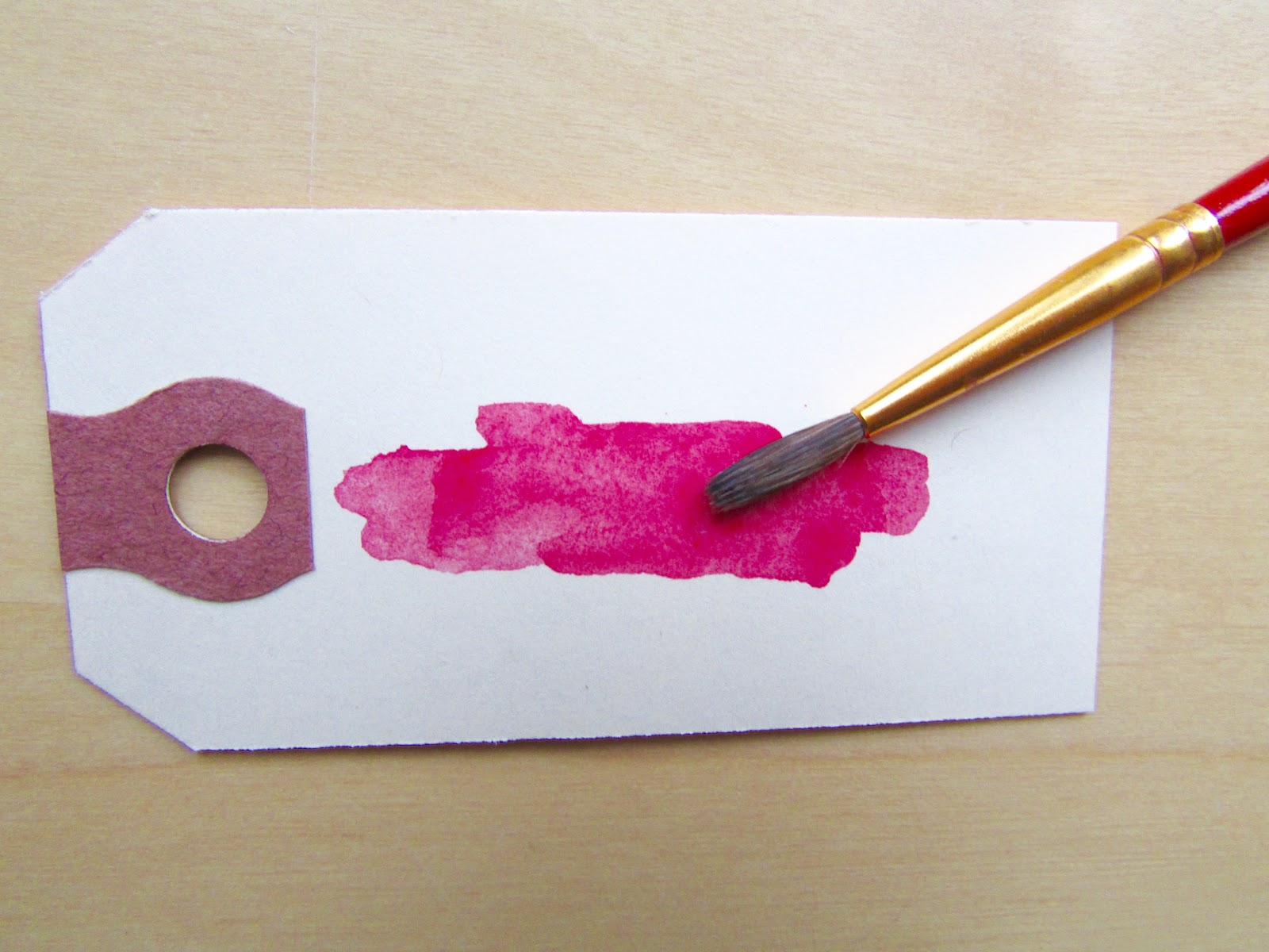 red watercolour brush strokes on shipping tag