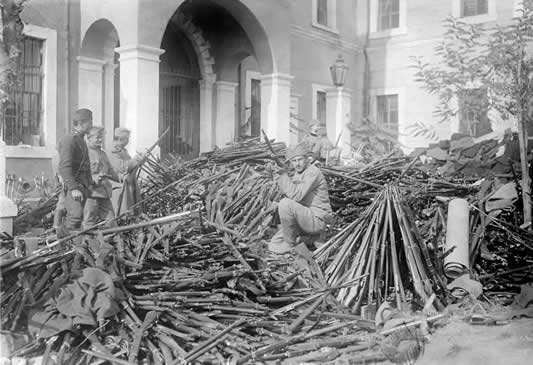 Serbian troops examining rifles, captured in large quantities from the Turks, at Skopje, October 1912