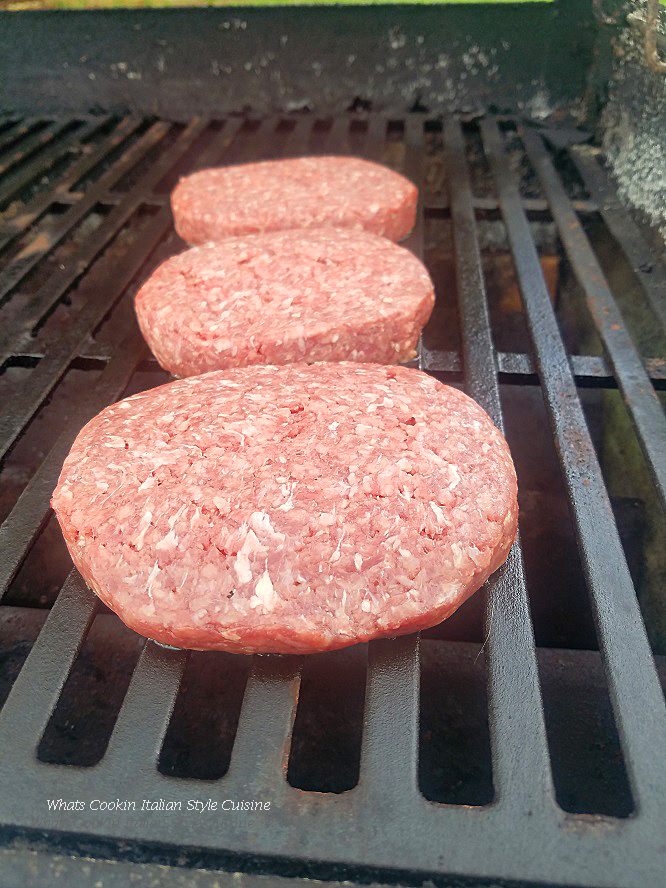 these are raw  hamburgers on a grill with a flame cooking on a low heat getting ready to be part of a delicious Alfredo provolone burger