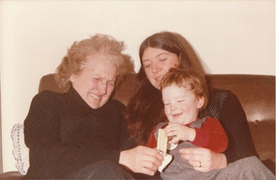 A lady laughing, a women holding a baby stretching for white chocolate.