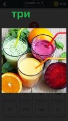 На столе стоят три стакана с трубочками разного цвета, лимон, разрезанный мандарин