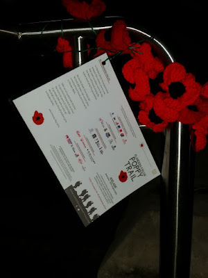 "A close-up of the poppies and attached leaflet which is a laminated tri-panel size (DL x 3). The front says, ""Flanders Fields Poppy Trail, Adelaide, 2nd June - 30th August 2016. A shared event throughout Adelaide, commemorating Australian, French and Belgian allies during WW1 with a range of cultural exhibitions, concerts, lectures and films.""  The centre panel is the back of the leaflet and contains the logos of supporting organisations and sponsors of the event. The panel towards the top has the poem ""In Flanders Fields"" by John McCrea printed. The words of this poem can be found on the Lupey Loops blog post called ""Poppy Patterns"" (April 2015)"