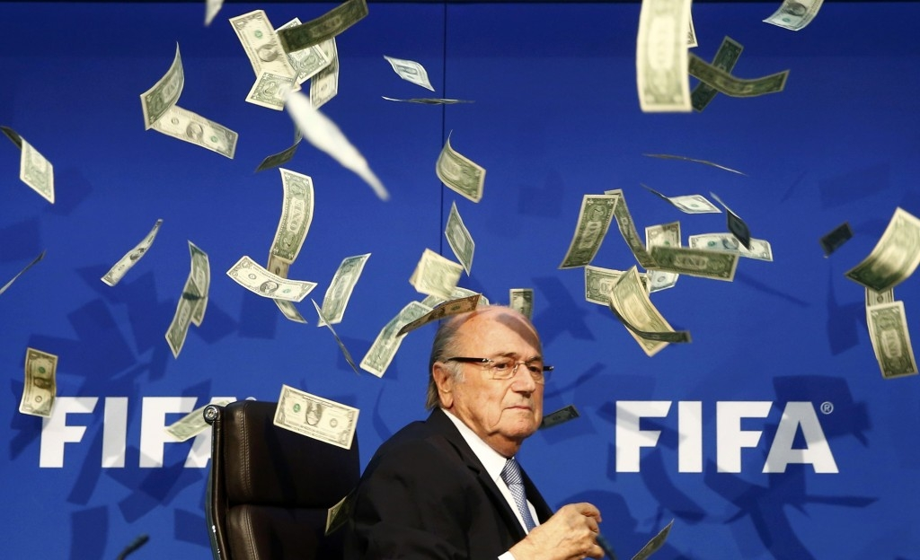 70 Of The Most Touching Photos Taken In 2015 - FIFA President Sepp Blatter has bank notes thrown at him during a press conference following accusations of corruption.