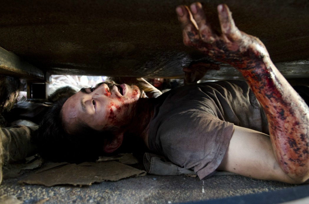 Glenn hiding under the dumpster