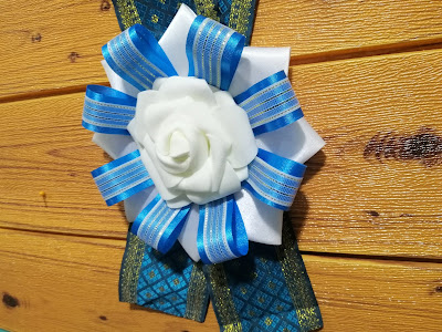 A combination of blue and white ribbon rosette with jacquard brocade trimming as lei, worm by a Filipino student during graduation ceremony.