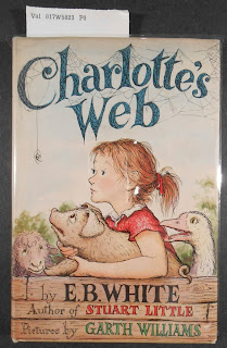"The cover of the book ""Charlotte's Web."" It shows a young  leaning holding a pig, with a goose and sheep to either side. She and the animals are looking at a spider, hanging by a thread from the ""C"" in the title."