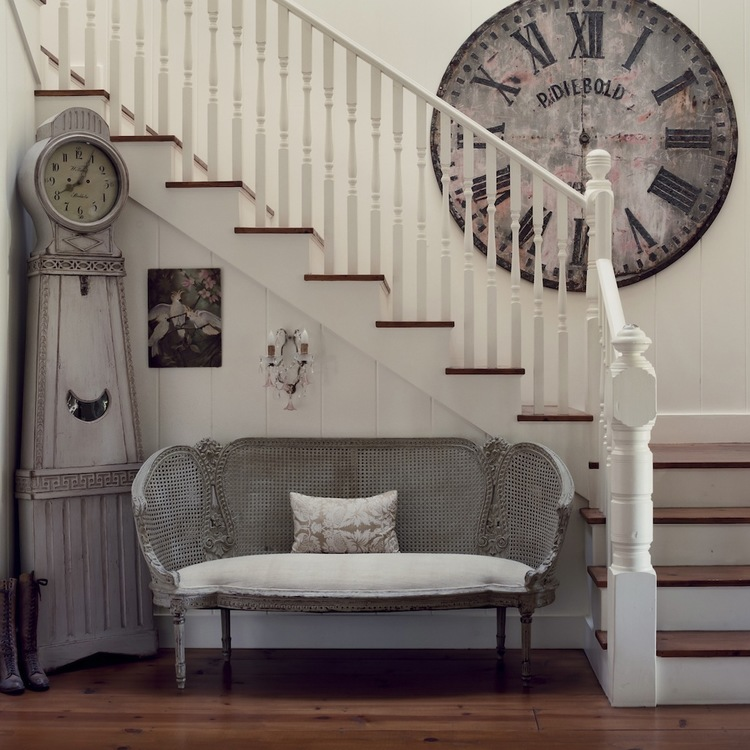 Entry with staircase and antique settee in California beach cottage in Santa Monica by Giannetti Home