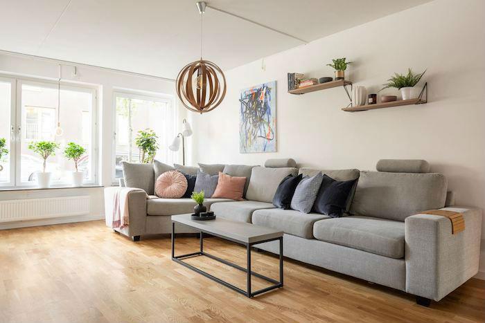 Salón con gran sofá en esquina y cables a la vista