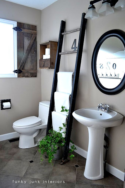 Farmhouse bathroom with ladder towel holder and crate toilet paper storage. Click for the full tour!