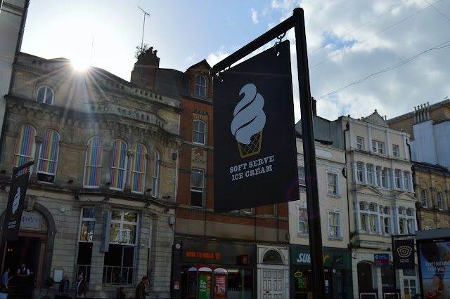 a flag advertising Pieminister with the sun shining across the buildings.
