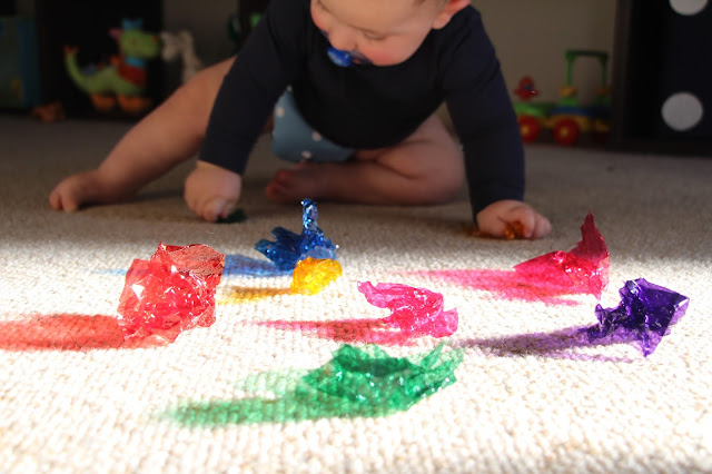 Baby playing with coloured cellophane in the sunlight