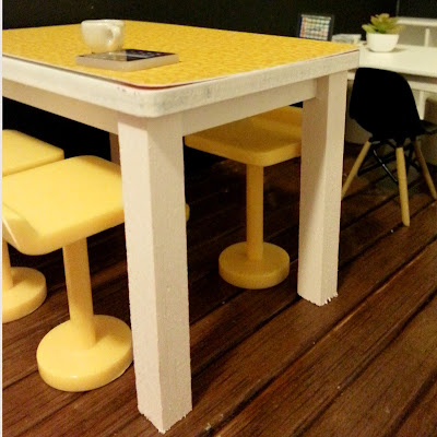 One-twelfth scale modern miniature high work table with white wooden legs and a yellow printed top. Around it are yellow high stools.