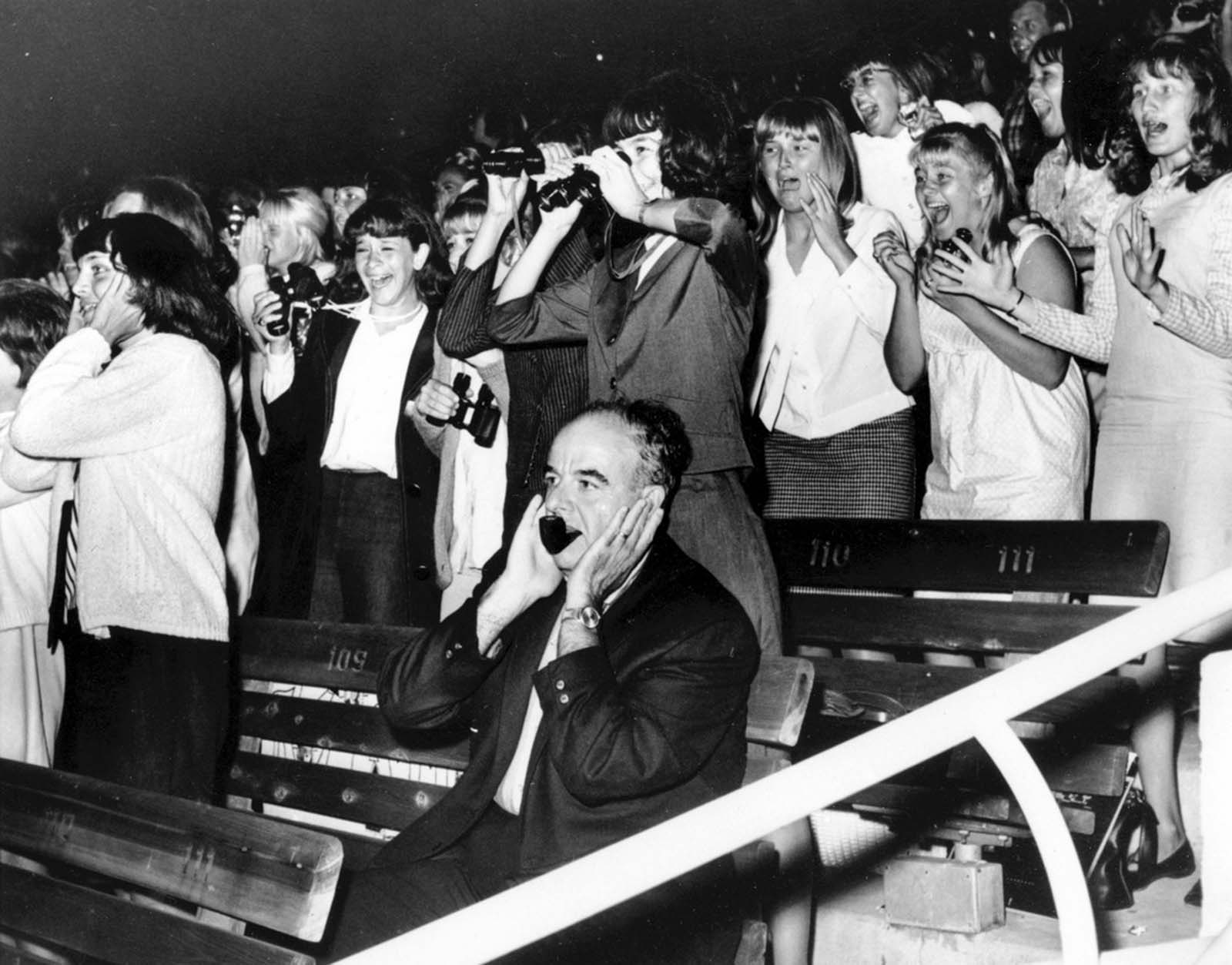 A man covers his ears as 18,000 screaming fans react to The Beatles in the Hollywood Bowl, California, during their U.S. concert tour on August 23, 1964.