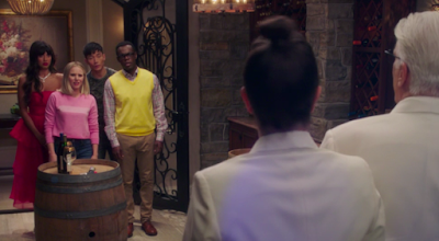 Tahani, Eleanor, Jason, and Chidi stand in a group by a large glass door. Michael and Janet are facing them, so we only see their backs. In between them, there's a wine barrel with bottles on it.
