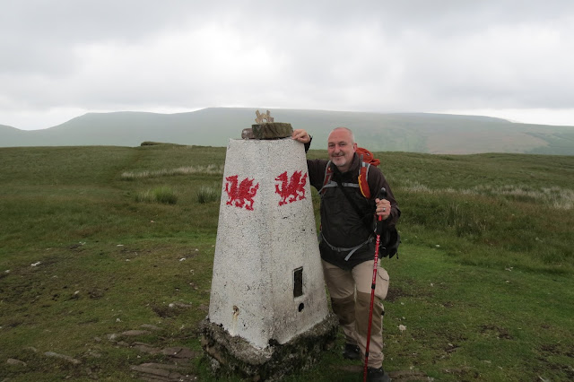 Me by an OS trig pillar, which is painted white and emblazoned with a red Welsh dragon on each face.