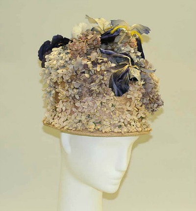 Elaborately decorated beige women's hat displayed on mannequin head