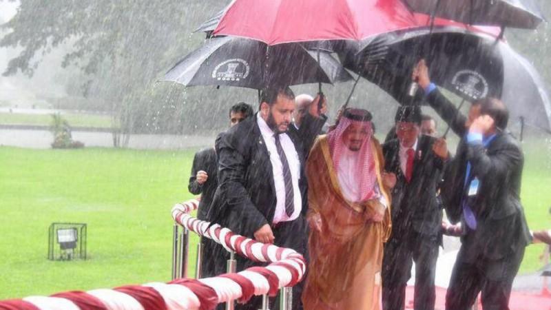 Jokowi memayungi dan menggandeng Raja Salman