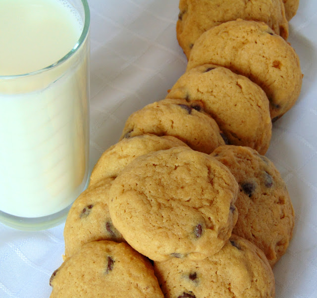 A pile of Favourite Soft Chocolate Chip Cookies with a glass of milk.