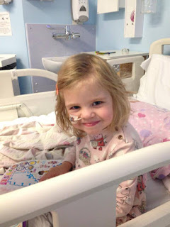 A little girl smiling whilst in a hospital bed
