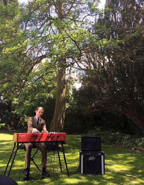 Man in suit playing Nord Electro 5D keyboard under tree at outdoor British wedding