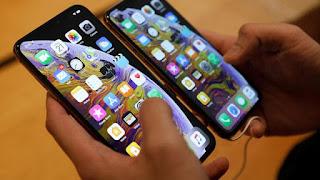 Calon pembeli membandingkan ukuran ponsel iPhone XS dan iPhone XS Max di Apple Store, Singapura, 21 September 2018. iPhone XS dan XS Max mempunyai sertifikasi IP68, yang dapat bertahan di air sedalam 2 meter selama 30 menit. REUTERS