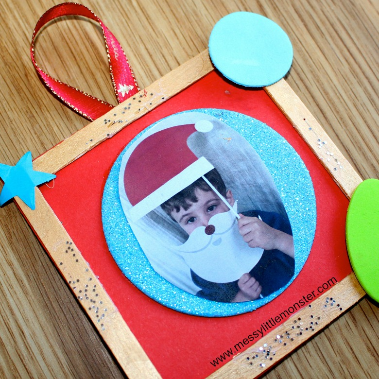 An easy Christmas photo frame craft for kids. Use craft sticks to make a personalised picture frame ornament.  Christmas props make the photo extra special.  Great activity for kids, preschoolers and toddlers.