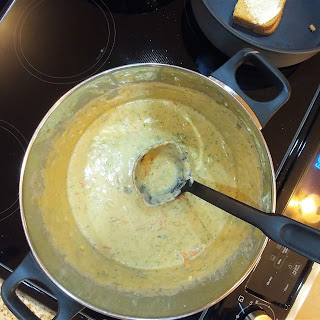 soup in a pot with a ladle in it; grilled cheese sandwich in the top right corner of stove