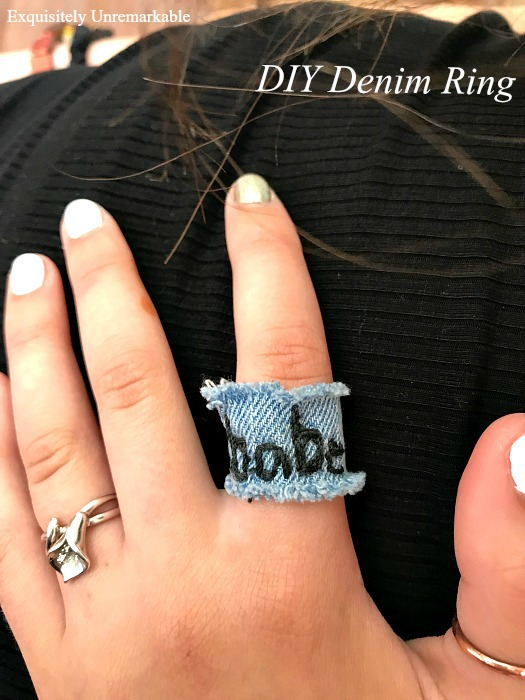 Babe embroidered on denim ring shown on hand with other rings