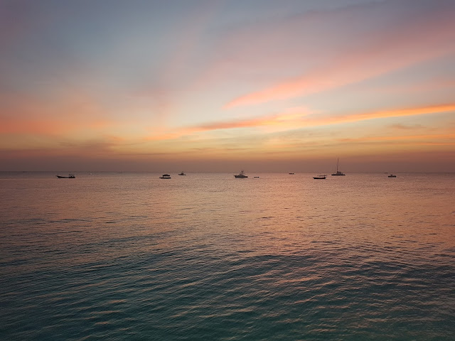 Sunset over the ocean, with boats in the distant foreground, as seen from Nungwi, Zanzibar