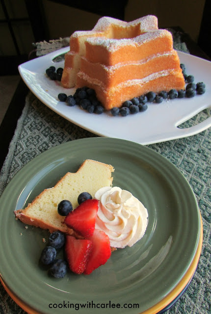 slice of sand torte served with strawberries, blueberries and cream cheese whipped cream
