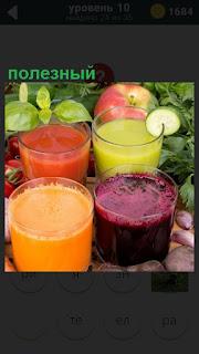 На столе стоят стаканы с разными полезными напитками и овощи рядом