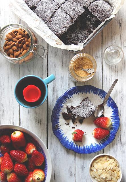 Tavolo con brownies al cioccolato, mandorle e fragole