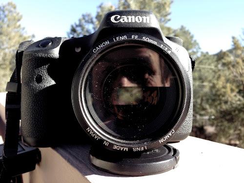 Clique de uma máquina fotográfica Canon com reflexo do fotógrafo na lente
