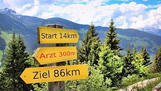 """Ein Wegweiser steht vor einer schönen Berglandschaft. Auf dem oberen Schild des Wegweisers, das nach rechts zeigt, steht """"Start 14 km"""". Das mittlere zeigt geradeaus und darauf steht """"Arzt 300m"""". Das untere zeigt nach links und trägt die Aufschrift """"Ziel 86km""""."""