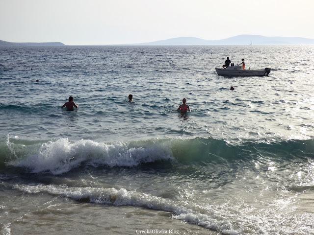 ludzie kąpiący się w greckim morzu w oddali łódka z trzema osobami